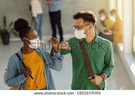 Happy university students greeting in a lobby and elbow bumping while wearing protective face masks.