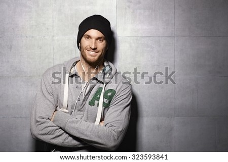 Happy urban man listening to music through earbuds, leaning against grey wall.