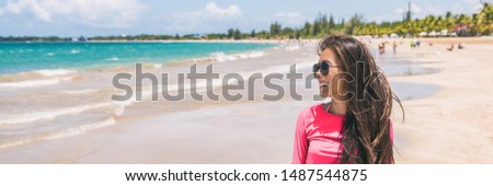 Happy vacation tourist woman relaxing on Puerto Rico beach banner panorama. Smiling young Asian girl in the sun, in sunglasses. #1487544875