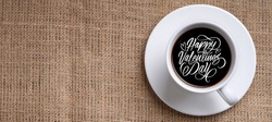 Happy valentine day black latter on cup of coffee on jute from top
