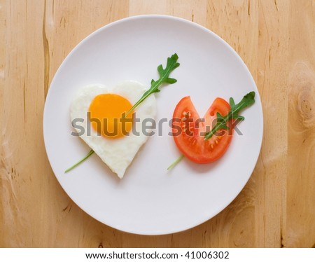 Happy Valentine Day! Fried egg and slice of tomato in the shape of two hearts pierced with two arrows