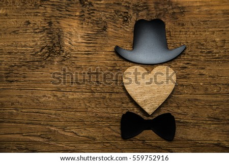 Happy Valentine's Day concept with tie, bow, hat and  red heart - face expressions. amour lie on wooden background. male personage. Valentines day card hearts image. empty copy space for inscription #559752916