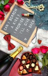 Happy Valentine's Day flat lay overhead with roses, chocolate gift box, champagne and letterboard spelling Can I Borrow a Kiss.