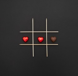 Happy Valentine's Day.  Game of tic-tac-toe with chocolate hearts with and without wrapper. black background and chalk inscription.