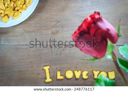 Happy Valentine\'s Day red roses on dark recycled wood background with word I Love You dessert