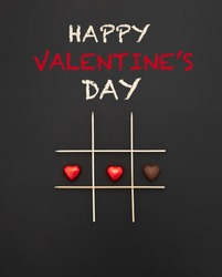 Happy Valentine's Day text. Game of tic-tac-toe with chocolate hearts with and without wrapper. black background and chalk inscription.