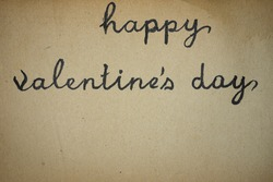 Happy valentine's day written with black ink on vintage paper. macro shot