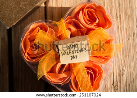 Happy Valentines Day and box with flowers in the shape of heart on the wooden background. Morning sunlight.