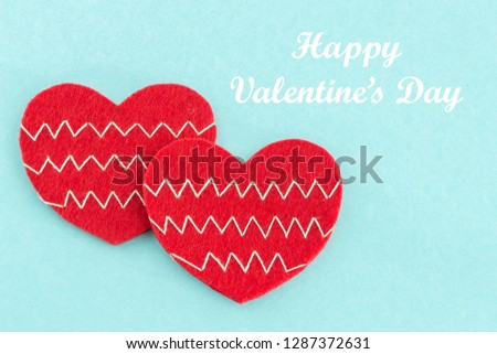 Happy valentines day card with beautiful handmade two toy hearts lying on color cardboard and text. Love, romance concept. Felt hearts with geometric zig zag embroidered lines. Stylish chevron pattern #1287372631