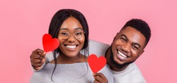 Happy Valentines day. Portrait of afro couple in love with red heart shaped cards, panorama