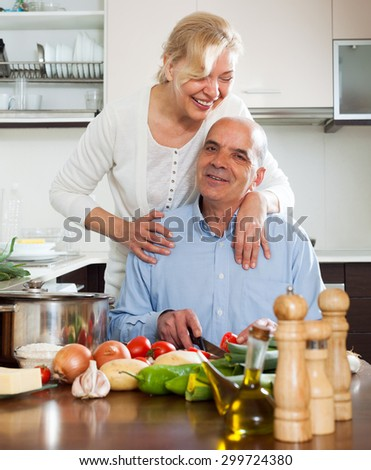 Happy vegetarian woman  smiling with senior and  cooking in domestic kitchen