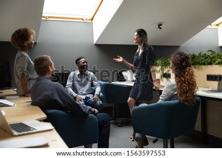 Happy vietnamese female team leader talking to smiling multiethnic group of colleagues, holding educational lecture workshop or sharing business project ideas together at modern coworking office.