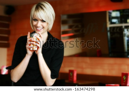 Happy vivacious young blond woman drinking orange juice or cocktail cradling the glass in her hands as she glances down at the floor