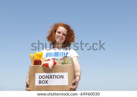 happy volunteer carrying food donation box