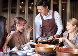 Happy waiter  bring  seafood  and serving group of friends in restaurant.