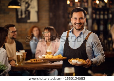Happy waiter holding plates with food and looking at camera while serving guests in a restaurant.  Stock photo ©