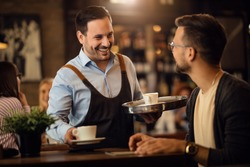 Happy waiter serving coffee and communicating with male guest in a bar.