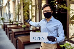 Happy waiter wearing protective face mask and holding open sign while reopening after COVID-19 epidemic.