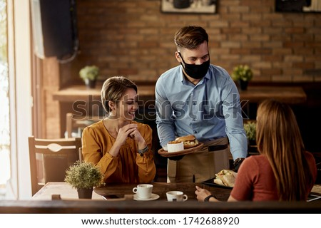 Happy waiter with protective face mask serving food to customers in a pub.