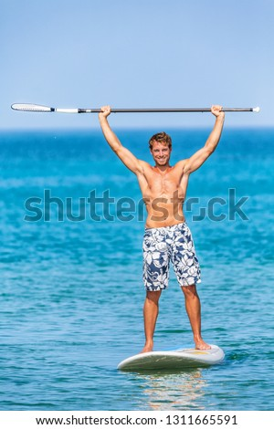 Happy watersport man having fun on stand-up paddleboard sup holding paddle up in the air in success on paddle board race. Handsome fit young athlete winning competition standing on surfboard.