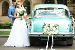 Happy wedding couple near decorated car, outdoors