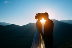 Happy wedding couple staying and kissing over the beautiful landscape with mountains during sunset