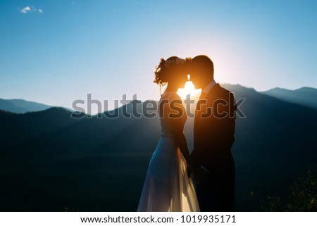 Happy wedding couple staying and kissing over the beautiful landscape with mountains during sunset #1019935171
