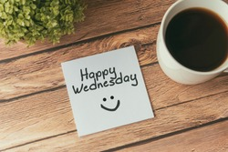Happy Wednesday with smile greeting on paper note with cup of coffee