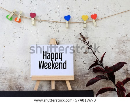 Happy Weekend - business concept words on canvas stand. rustic wooden background