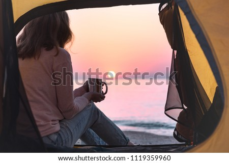 happy weekend by the sea - girl  in a tent on the beach at dawn. Ukrainian landscape at the Sea of Azov, Ukraine