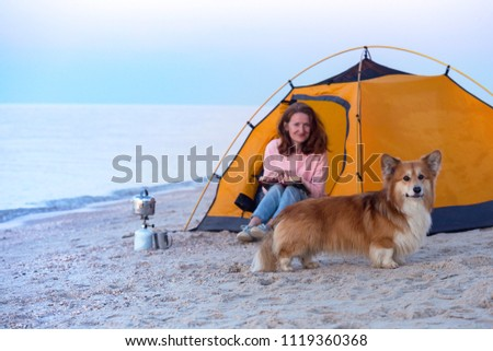 happy weekend by the sea - girl with a dog in a tent on the beach at dawn. Ukrainian landscape at the Sea of Azov, Ukraine