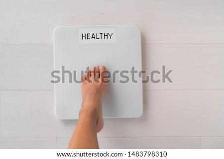 Happy weight loss woman stepping on scale weighting healthy weight after diet goal challenge. Top view of foot step on balance showing screen with good news text.