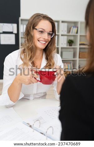 Happy White Office Girl Wearing Long Sleeve Shirt and Eyeglasses, Having Coffee Break with Co-worker at her Worktable.