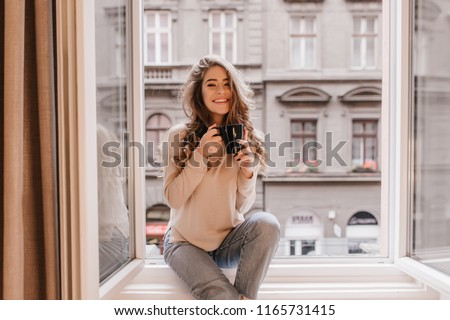Happy white woman with gorgeous hairstyle sitting on window sill. Indoor portrait of glad young lady in jeans posing emotionally while drinking coffee.
