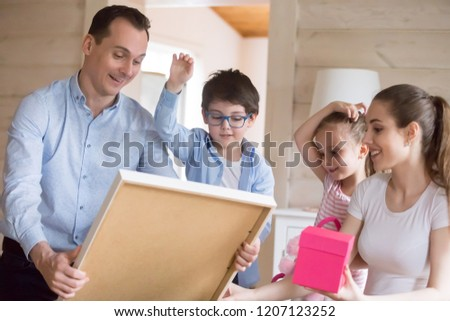 Happy whole family spend time together at home. Attractive positive mother handsome father with adorable kids son daughter have fun celebrate event holiday or move at new house unpack their belongings