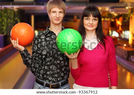 happy wife and husband with balls stand in bowling club and look at camera