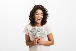 Happy winner american woman with afro hairstyle and big smile holding money prize dollar cash isolated over white background
