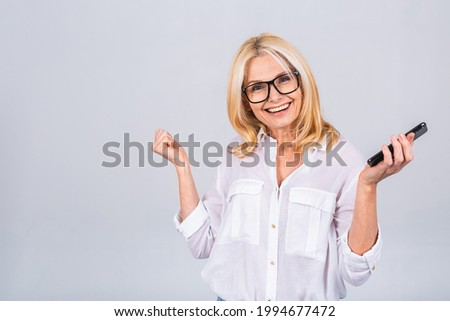 Happy winner! Photo of crazy ecstatic mature senior woman use smartphone impressed social media like feedback win raise fists scream yes isolated over white grey background Foto stock ©