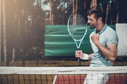 Happy winner. Side view of happy young man in polo shirt holding tennis racket and gesturing while standing on tennis court