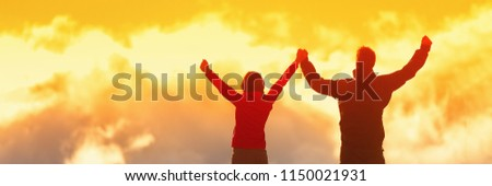 Happy winners reaching life goal - success people at summit. Business achievement concept. Two person couple together arms up in air in the clouds at sunset panoramic banner.