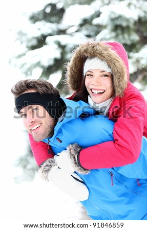 Happy winter couple piggybacking in snow smiling and joyful at camera. Beautiful young multi-ethnic couple, Asian mixed-race woman, Caucasian man doing piggyback.