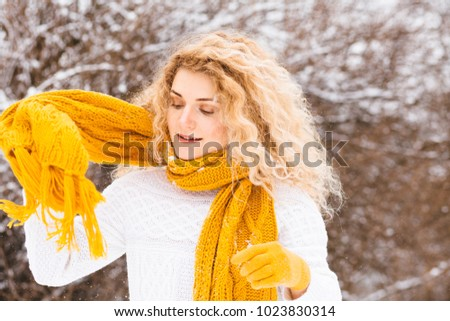 Happy winter fun woman in white sweater and yellow scarf playing throwing snow in freedom enjoying the cold season. Winter mood concept.