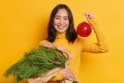 Happy winter holidays concept. Cheerful Asian woman has festive mood holds bouquet of fir tree branches and big glass bauble toy going to decorate and prepares for coming New Year or Christmas