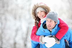 Happy winter travel couple. Man giving woman piggyback ride on winter vacation in snowy forest. Young interracial couple, Asian woman, Caucasian man.