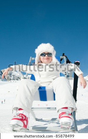 Happy winter vacation - little skier in ski resort (copy space, cover)