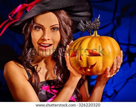Happy witch holding pumpkin on dark blue background.