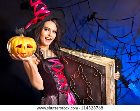 Happy witch woman holding old book and pumpkin.