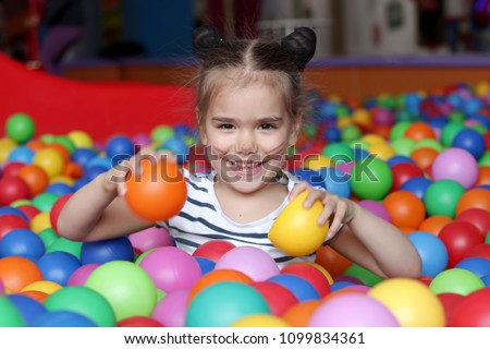 Happy with aqua makeup on her face playing and having fun at kindergarten with colorful balls, family weekend concept, happy birthday and merry party #1099834361