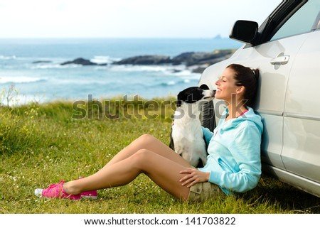 Happy woman and dog sitting outside car on summer travel vacation. Pet and human friendship and traveling concept. Relaxing and enjoying peace on nature together.