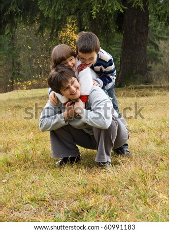 Happy woman and her children playing outside in autumn time